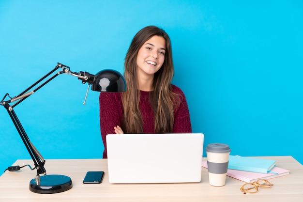 Jugendlichmädchen mit einem laptop in einem tabellenlachen