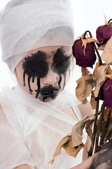 Jugendlichmädchen mit mamaverbänden auf halloween auf weiß lokalisiert