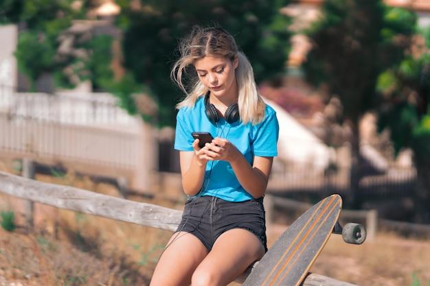 Jugendlichmädchen mit rochen am freien, das eine mitteilung mit dem mobile sendet