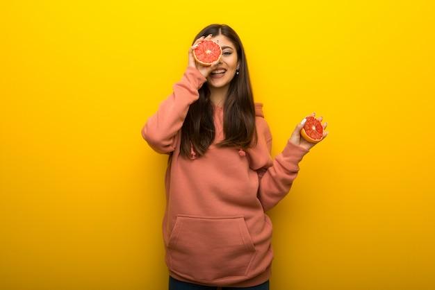 Jugendlichmädchen mit rosa sweatshirt auf gelbem hintergrund mit orangen