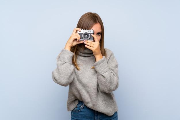 Jugendlichmädchen mit strickjacke über dem getrennten anhalten einer kamera