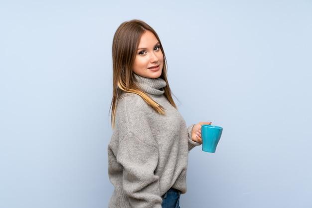 Jugendlichmädchen mit strickjacke über dem lokalisierten blau, das heißen tasse kaffee hält