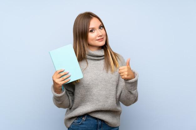 Jugendlichmädchen mit strickjacke über dem lokalisierten blauen hintergrund, der ein buch hält und liest