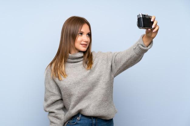 Jugendlichmädchen mit strickjacke über dem lokalisierten blauen hintergrund, der ein selfie macht
