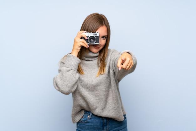 Jugendlichmädchen mit strickjacke über dem lokalisierten blauen hintergrund, der eine kamera hält