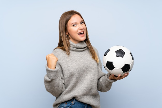 Jugendlichmädchen mit strickjacke über dem lokalisierten blauen hintergrund, der einen fußball hält
