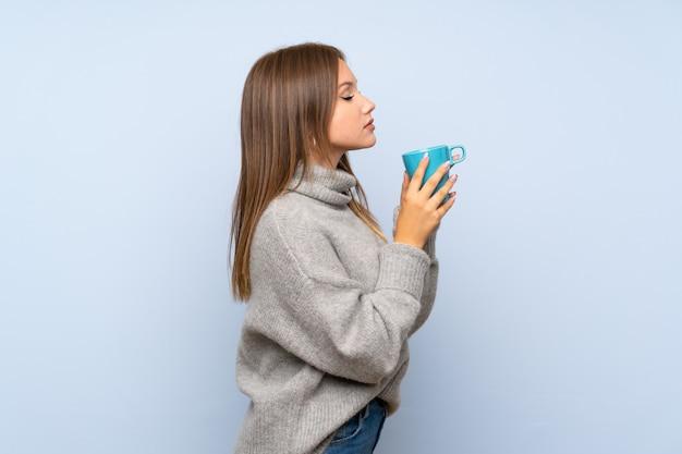 Jugendlichmädchen mit strickjacke über dem lokalisierten blauen hintergrund, der heißen tasse kaffee hält