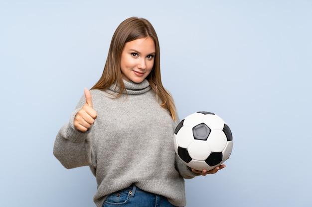 Jugendlichmädchen mit strickjacke über dem lokalisierten halten eines fußballs