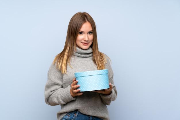 Jugendlichmädchen mit strickjacke über lokalisierter haltener geschenkbox