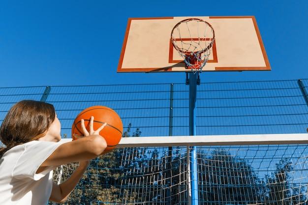 Jugendlichmädchen-straßenbasketballspieler mit ball