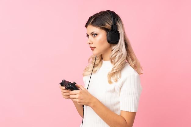 Jugendlichmädchen über dem lokalisierten rosa hintergrund, der an den videospielen spielt
