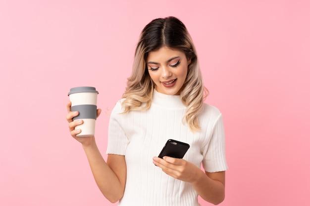 Jugendlichmädchen über dem lokalisierten rosa hintergrund, der kaffee hält, um und ein mobile wegzunehmen