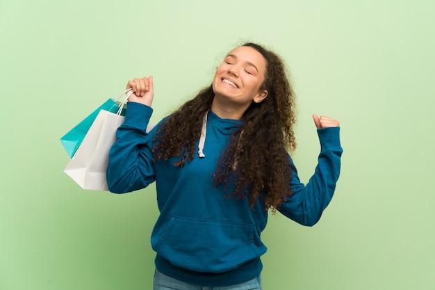 Jugendlichmädchen über der grünen wand, die viele einkaufstaschen in siegposition hält