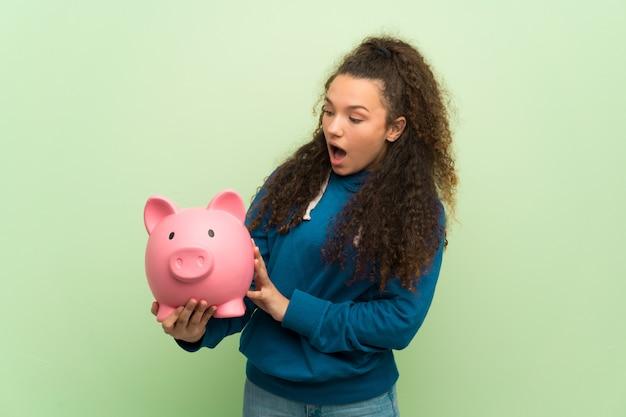 Jugendlichmädchen über der grünen wand überrascht beim halten eines sparschweins