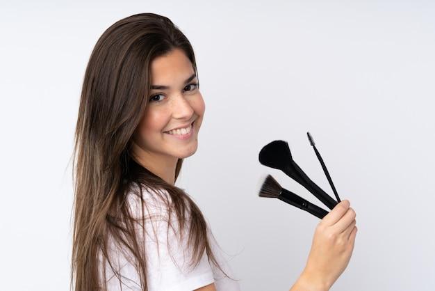 Jugendlichmädchen über der lokalisierten wand, die make-upbürste hält