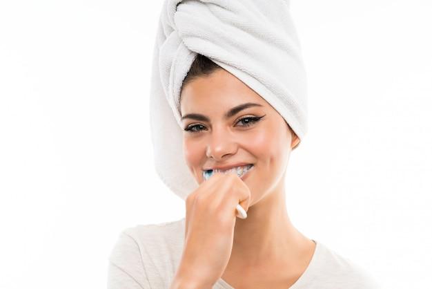 Jugendlichmädchen über der lokalisierten weißen wand, die ihre zähne putzt