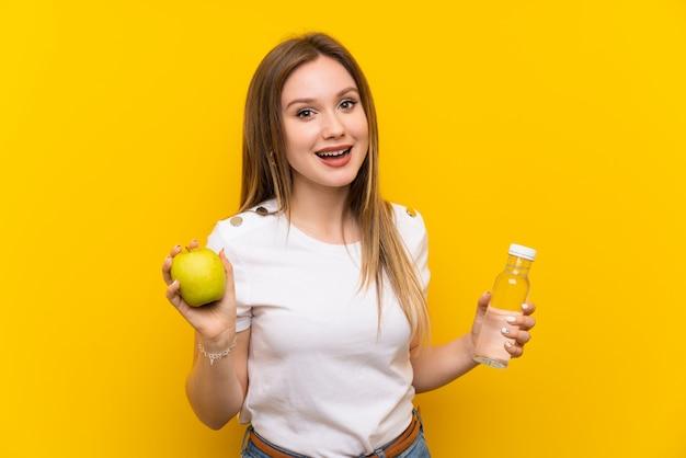 Jugendlichmädchen über gelber wand mit einem apfel und einer flasche wasser