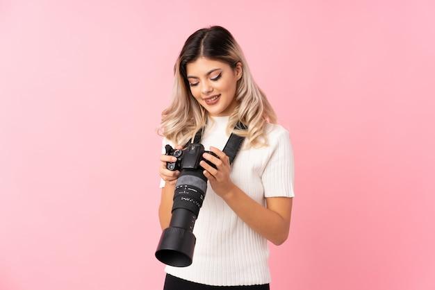 Jugendlichmädchen über getrenntem rosa mit einer berufskamera