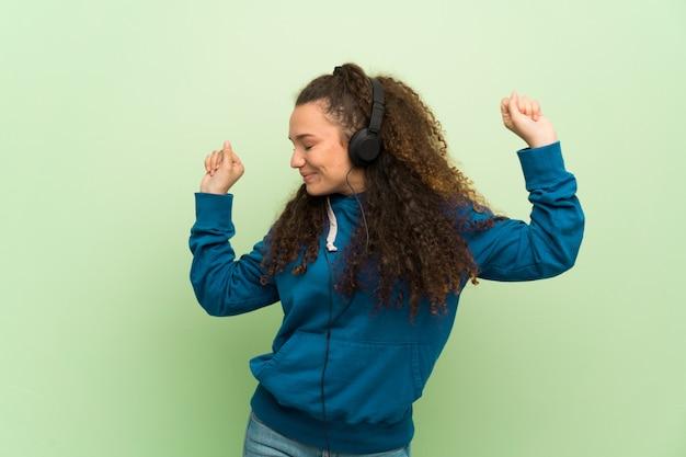 Jugendlichmädchen über grüner wand hörend musik mit kopfhörern und tanzen