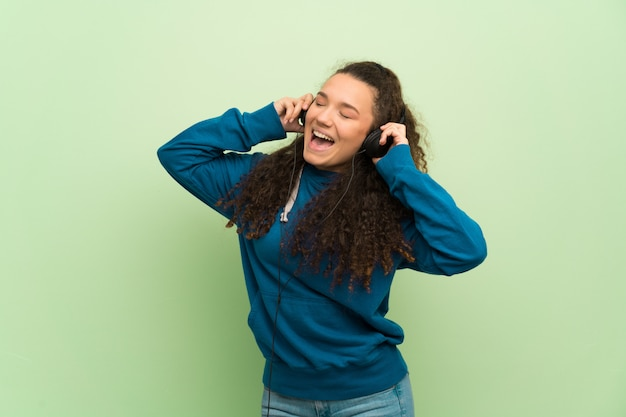 Jugendlichmädchen über grüner wand hörend musik mit kopfhörern