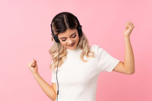 Jugendlichmädchen über lokalisiertem rosa unter verwendung des mobiles mit kopfhörern und tanzen