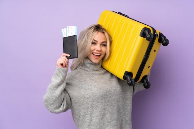 Jugendlichmädchen über lokalisierter purpurroter wand in den ferien mit koffer und pass