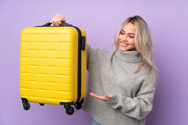 Jugendlichmädchen über lokalisierter purpurroter wand in den ferien mit reisekoffer