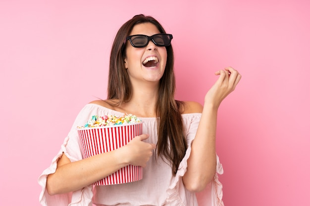 Jugendlichmädchen über lokalisierter rosa wand mit gläsern 3d und dem halten eines großen eimers popcorns