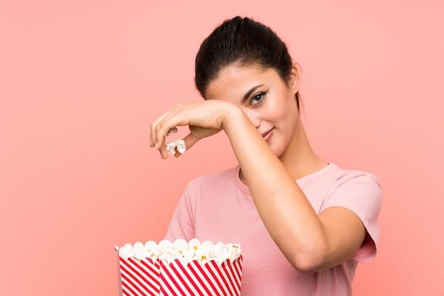 Jugendlichmädchen über lokalisierter rosa wand popcorn essend