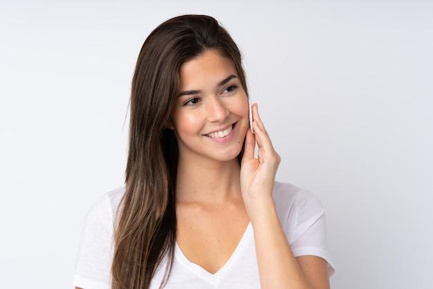 Jugendlichmädchen über lokalisierter wand mit baumwollauflage für das entfernen von make-up von ihrem gesicht