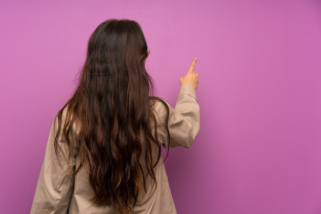 Jugendlichmädchen über purpurroter wand zurück zeigend mit dem zeigefinger