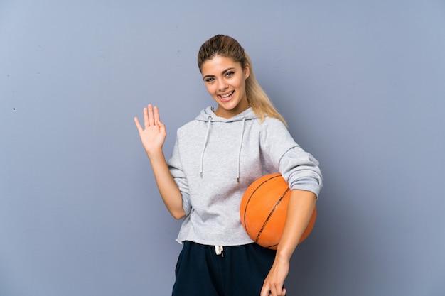 Jugendlichmädchen, welches den basketball begrüßt mit der hand mit glücklichem ausdruck spielt
