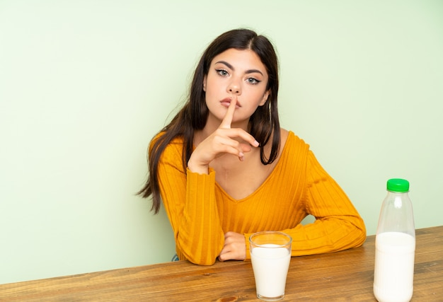 Jugendlichmädchen, welches die frühstücksmilch bildet ruhegeste isst