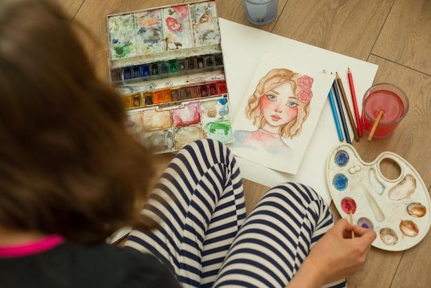 Jugendlichmädchen zeichnet mit aquarellen, bleistifte