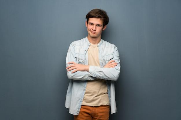 Jugendlichmann mit baumwollstoffjacke über der grauen wand, die gestört glaubt