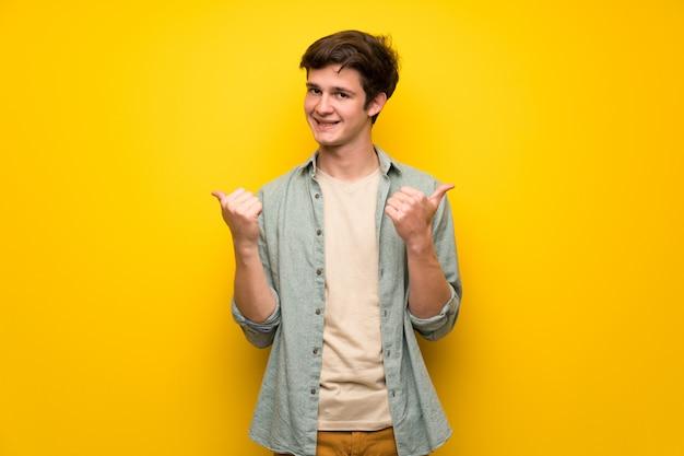 Jugendlichmann über dem gelben wandgeben daumen up geste mit beiden händen und dem lächeln