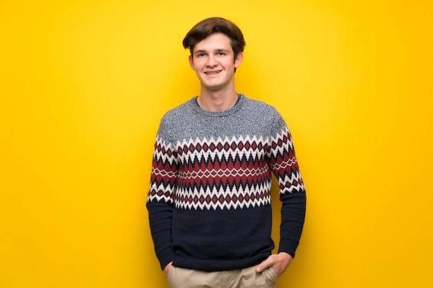 Jugendlichmann über gelber wand lachend nach vorne schauend