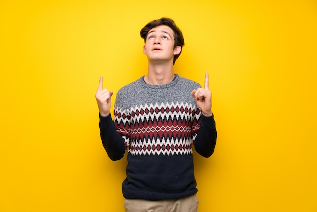 Jugendlichmann über gelber wand oben zeigend und überrascht