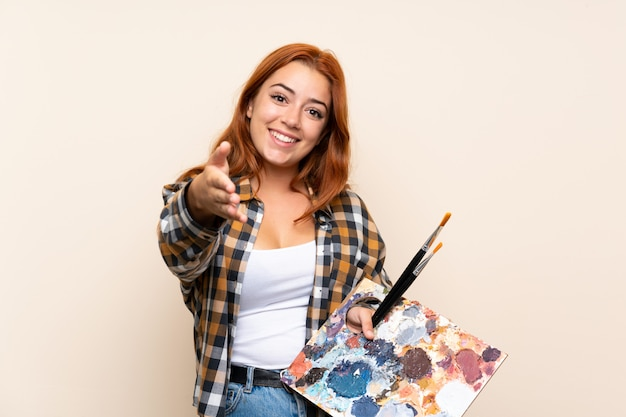 Jugendlichrothaarigemädchen, das ein palettenhändeschütteln nach viel hält