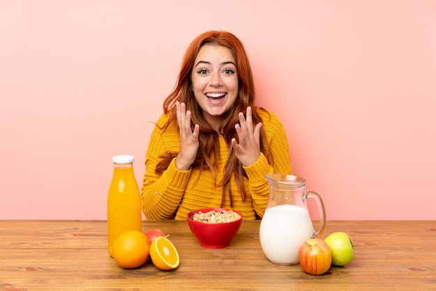 Jugendlichrothaarigemädchen, das in einer tabelle mit überraschungsgesichtsausdruck frühstückt