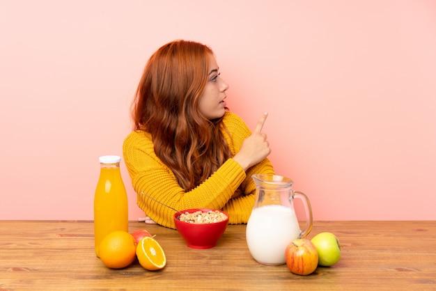 Jugendlichrothaarigemädchen, das in einer tabelle zurück zeigt mit dem zeigefinger frühstückt