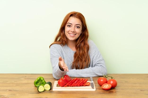Jugendlichrothaarigemädchen mit gemüse in einem tabellenhändeschütteln nach viel