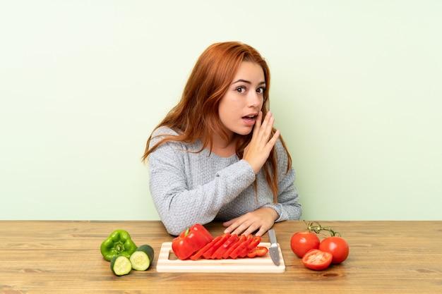 Jugendlichrothaarigemädchen mit gemüse in einer tabelle etwas flüsternd
