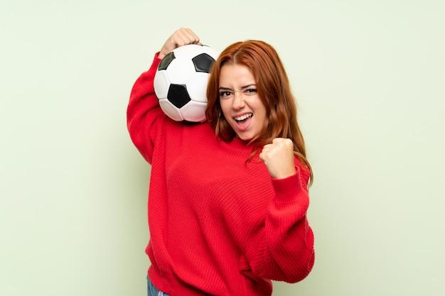Jugendlichrothaarigemädchen mit strickjacke über dem lokalisierten grün, das einen fußball hält