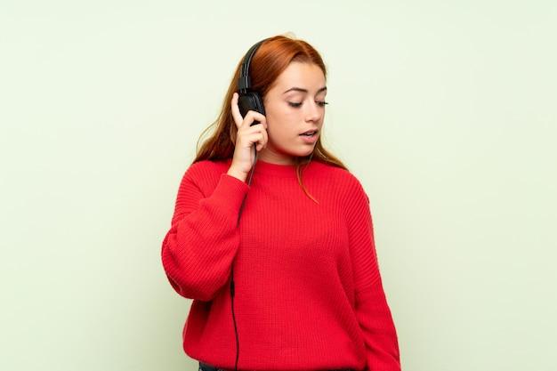Jugendlichrothaarigemädchen mit strickjacke über lokalisiertem grün hörend musik mit kopfhörern