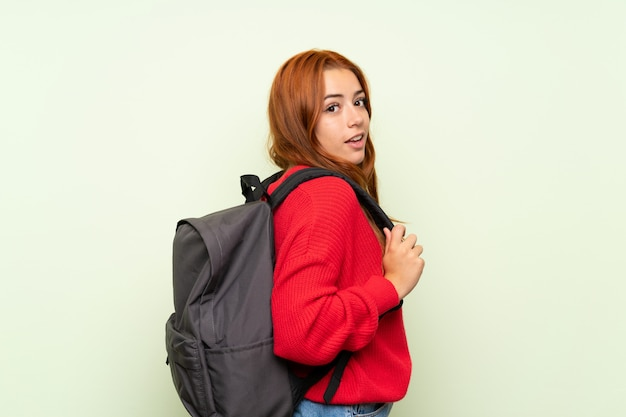 Jugendlichrothaarigemädchen mit strickjacke über lokalisiertem grün mit rucksack
