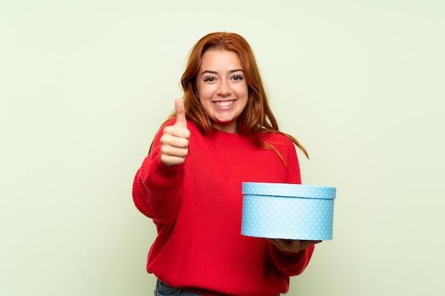 Jugendlichrothaarigemädchen mit strickjacke über lokalisierter grüner haltener geschenkbox