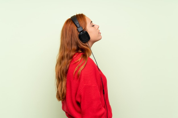 Jugendlichrothaarigemädchen mit strickjacke über lokalisierter grüner wand hörend musik mit kopfhörern