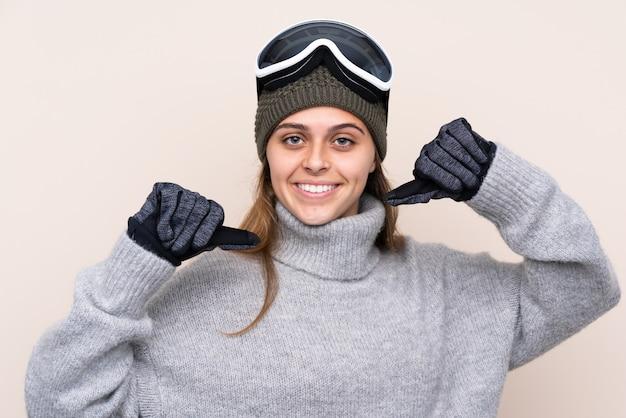 Jugendlichskifahrerfrau mit snowboardinggläsern über lokalisierter wand stolz und selbstzufrieden