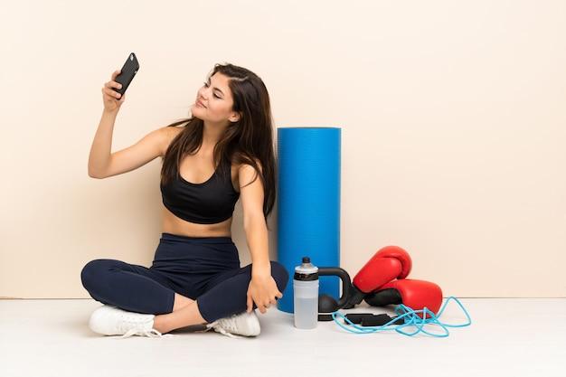 Jugendlichsportmädchen, das auf dem boden macht ein selfie sitzt